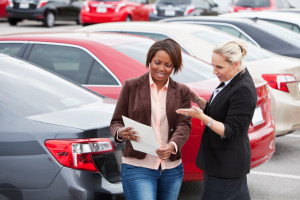 Woman shopping for a new car, with a saleswoman.  Shallow DOF, focus on foreground.